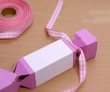 Tie the ribbon around the edges of the candy from the paper